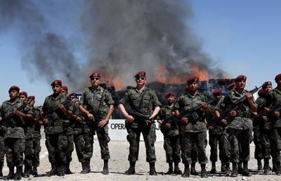Mexican Army soldiers stand at attention as drugs are destroyed by fire behind them in Ciudad Juarez.jpeg